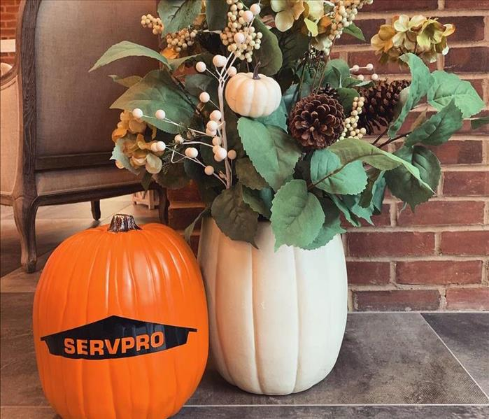SERVPRO pumpkin next to fall decoration on the floor in SERVPRO lobby