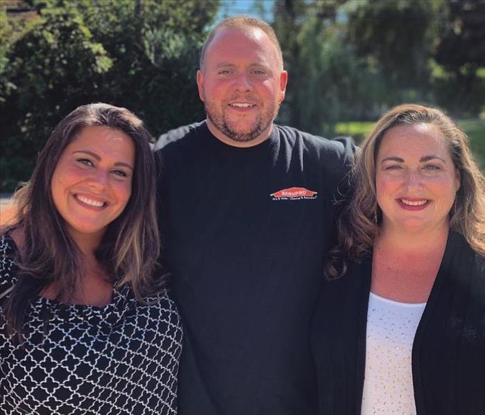2 female and 1 male SERVPRO employees,  smiling outside in sunny weather