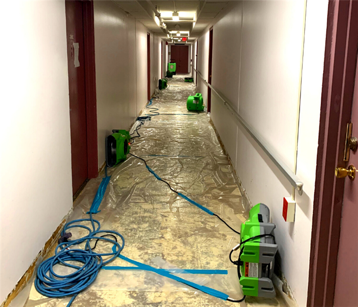 hallway of flooded apartment building with drying equipment positioned throughout